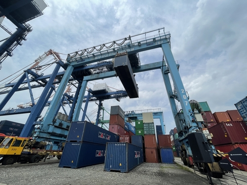 An automated yard crane, equipped with sensors and 5G network infrastructure, picks up a cargo container at Busan Port, 453 kilometers southeast of Seoul, on April 30, 2021. (Yonhap)