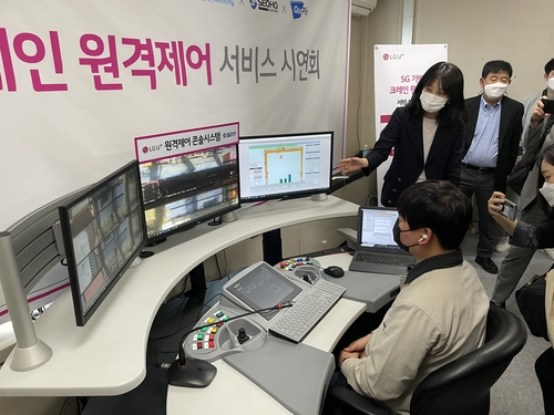 A crane operator monitors the automated machine at an office in Busan Port, 453 kilometers southeast of Seoul, on April 29, 2021. (Yonhap)
