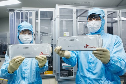 Employees of SK Innovation Co. present lithium-ion batteries for electric vehicles in this photo provided by the refinery-to-battery maker on July 30, 2020. (PHOTO NOT FOR SALE) (Yonhap)