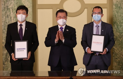 South Korean President Moon Jae-in (C) poses for a photo with John Rim (L), CEO of Samsung Biologics, and Stephane Bancel, CEO of Moderna, at a hotel in Washington, D.C. on May 22, 2021. (Yonhap)